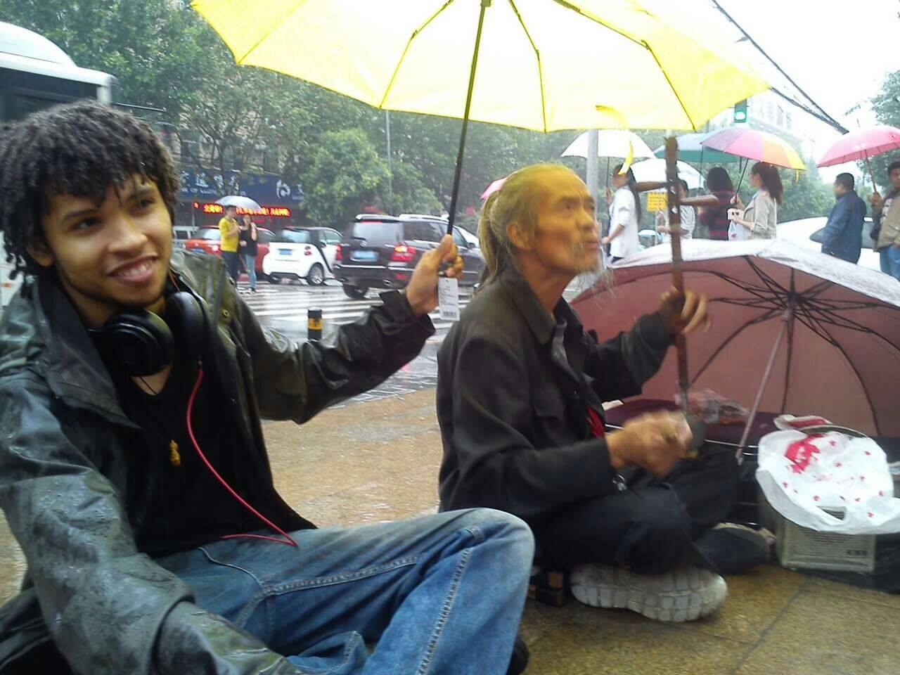 Shielding a homeless man from the rain as he busked on the street in Xi'an, China.