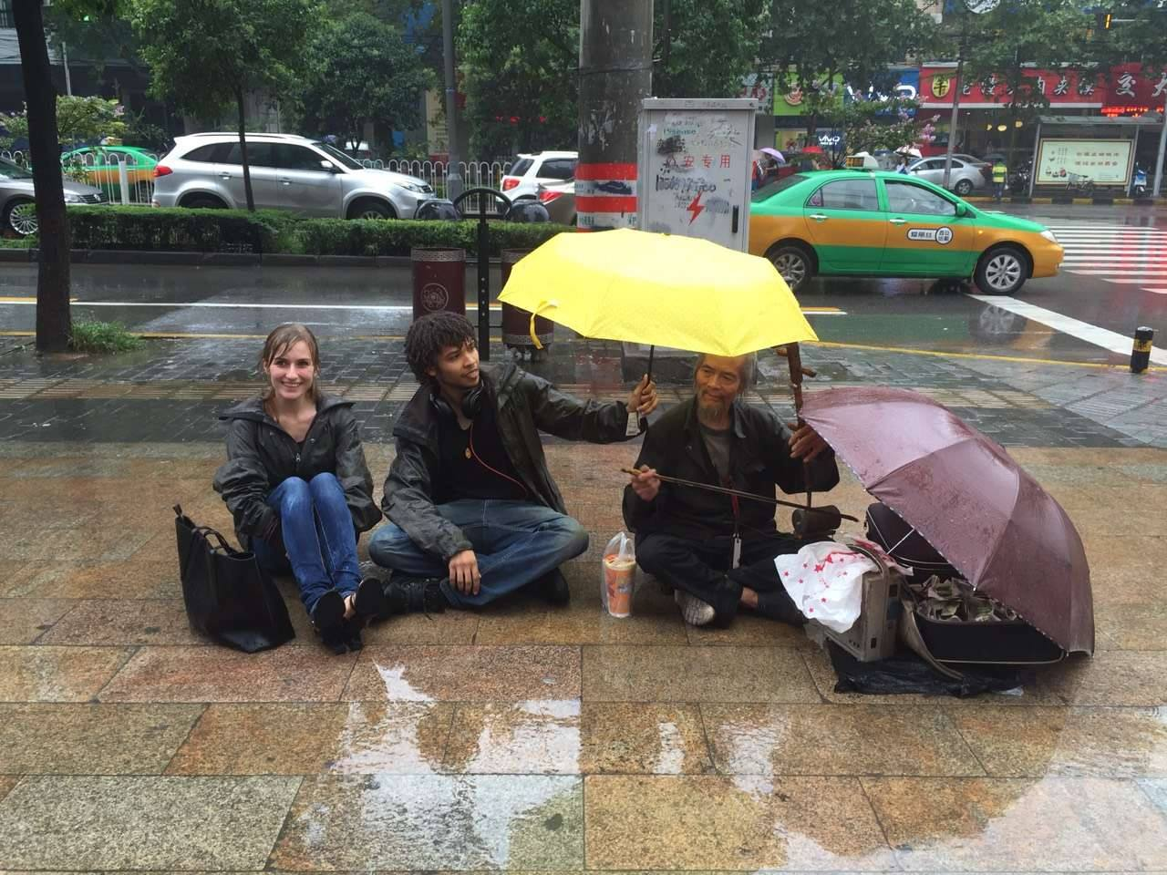Shielding a homeless musician from the rain in China. [Ref. Flora's Testimonial]